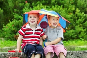 12374471-two-funny-kids-friends-sitting-under-umbrella-outdoor-summer--spring-season
